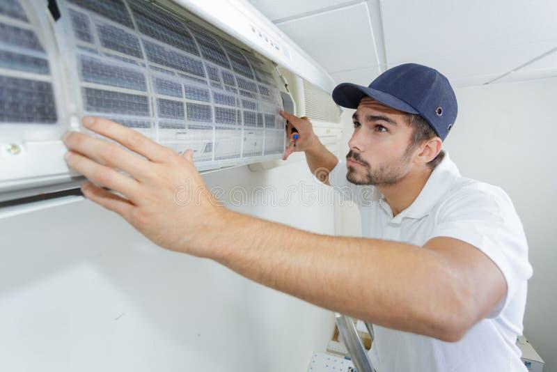 修理空调器的画象中间成人男性技术员 免版税库存照片