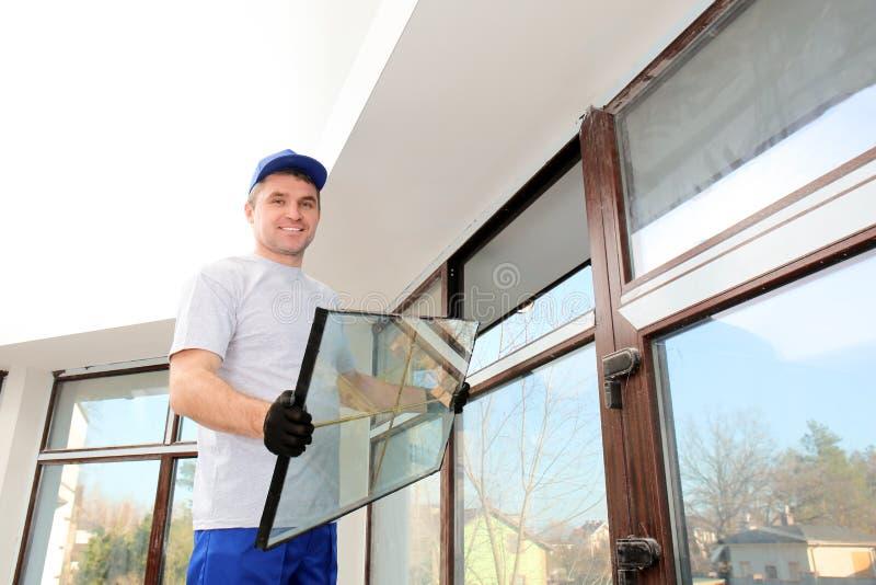 修理窗口的建筑工人 免版税库存图片
