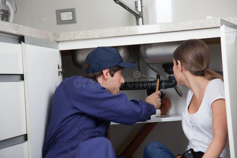 修理管子的夫妇水管工 库存图片