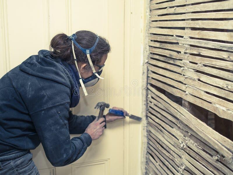 修理篱笆条和涂抹墙壁的少妇 免版税库存照片