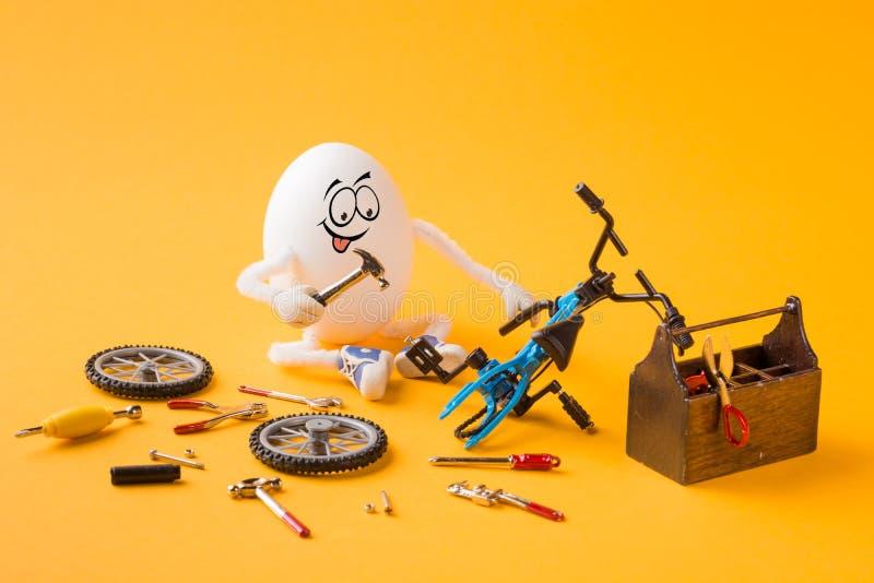 修理自行车的滑稽的被集中的鸡蛋 免版税库存照片