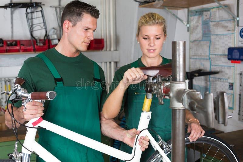 修理自行车的自行车技工和学徒 图库摄影