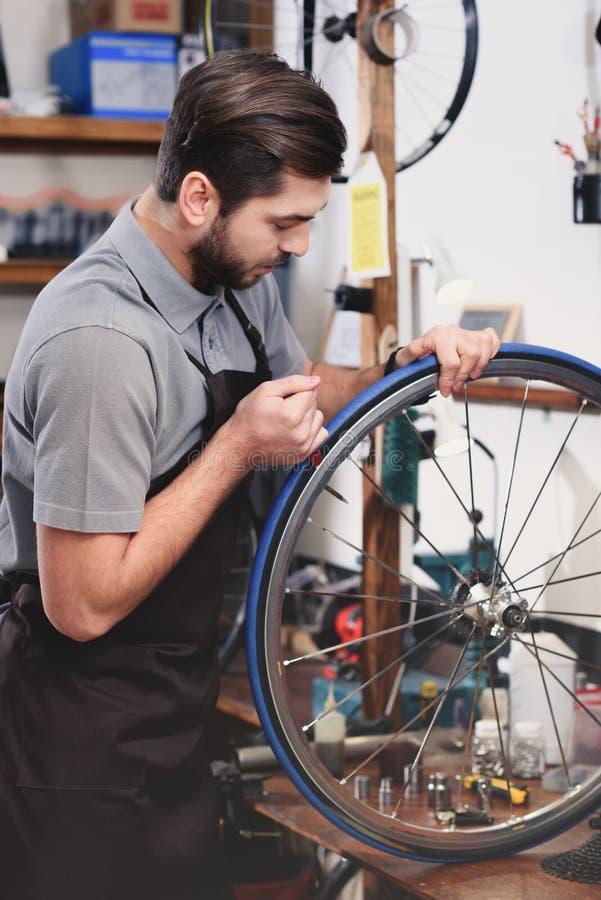 修理自行车车轮的围裙的年轻技工 库存照片