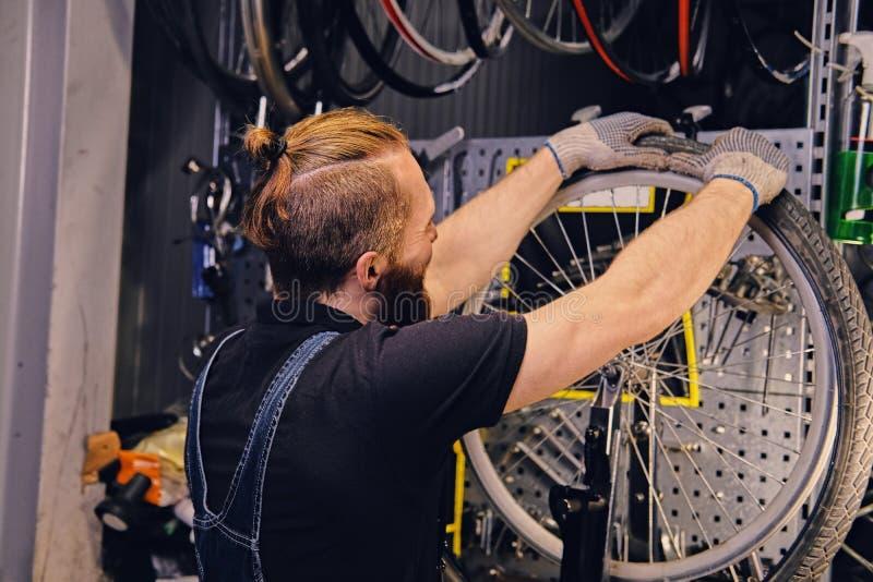 修理自行车车轮轮胎的技工在车间 免版税库存照片