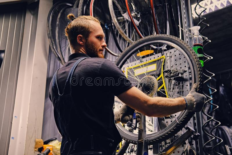 修理自行车车轮轮胎的技工在车间 库存照片