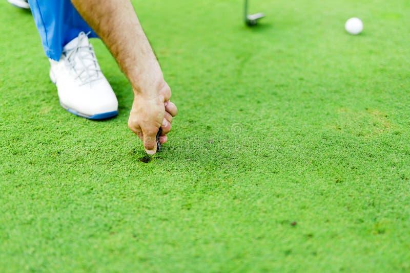 修理草皮的高尔夫球运动员 免版税库存照片