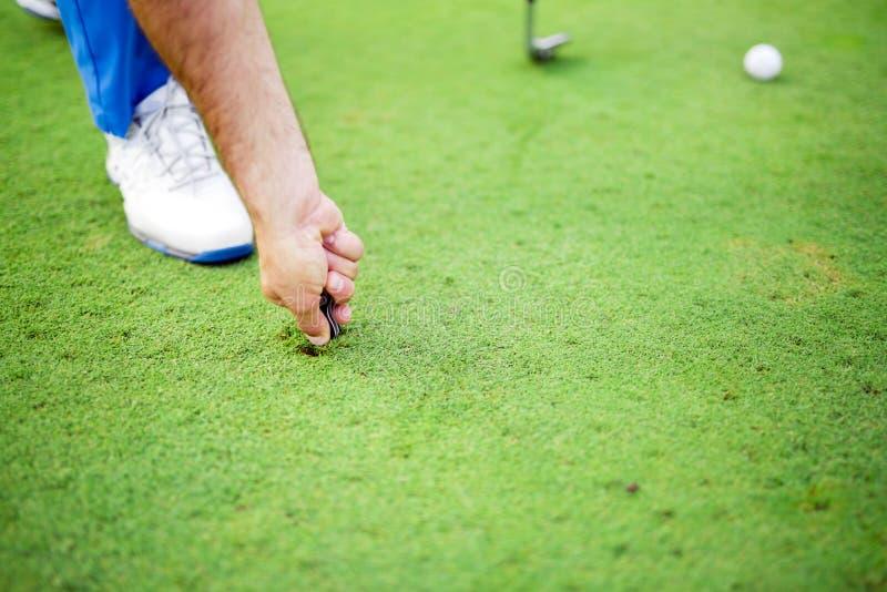 修理草皮的高尔夫球运动员 免版税库存图片
