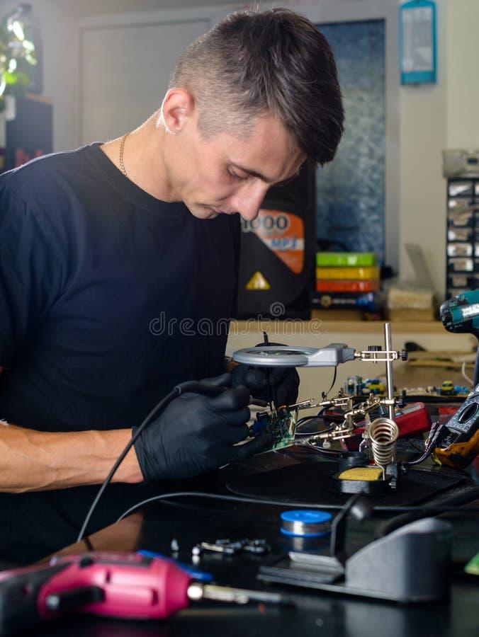 修理计算机的专业安装工在车间 图库摄影