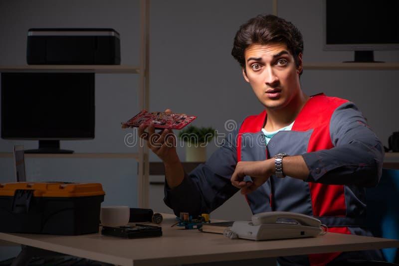 修理计算机的年轻英俊的安装工 库存图片
