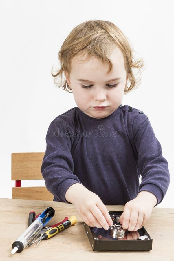修理计算机零件的小女孩 免版税库存图片