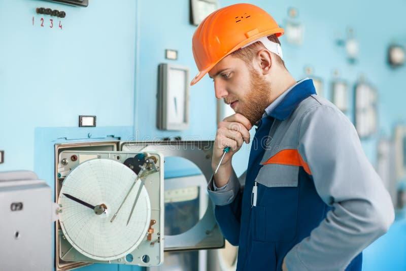 修理设备的年轻工程师在控制室 库存照片