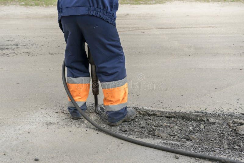 修理路 工作者修理路 人与手提凿岩机一起使用 库存图片