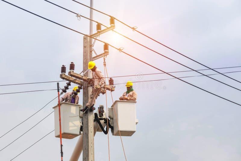 修理输电线的导线的与桶水力举的平台的电工 免版税库存照片