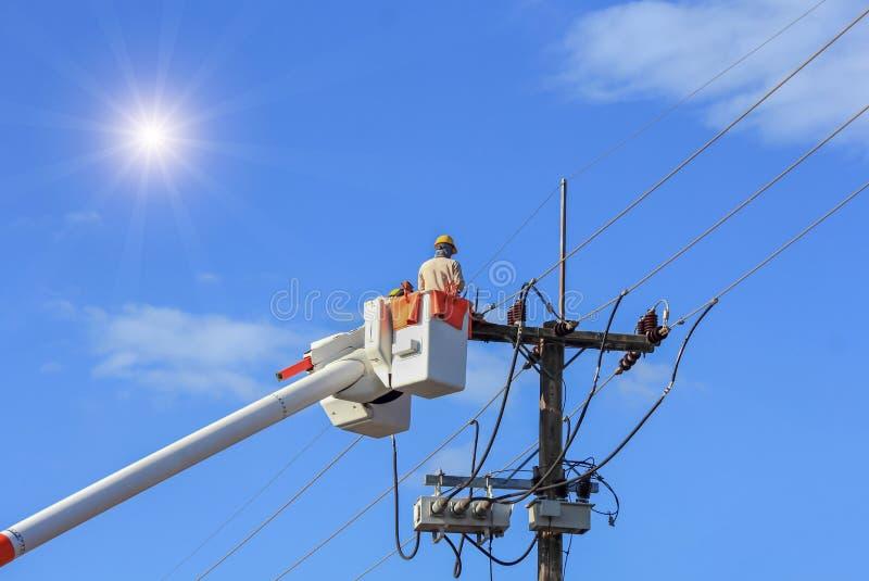 修理输电线的导线的与桶水力举的平台的电工 图库摄影