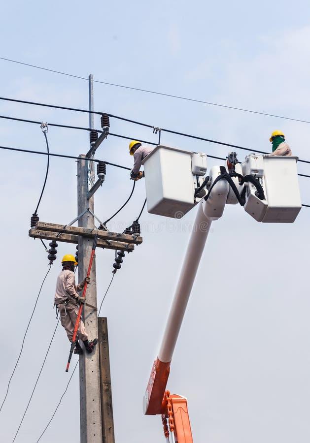 修理输电线的导线的与桶水力举的平台的电工 库存图片