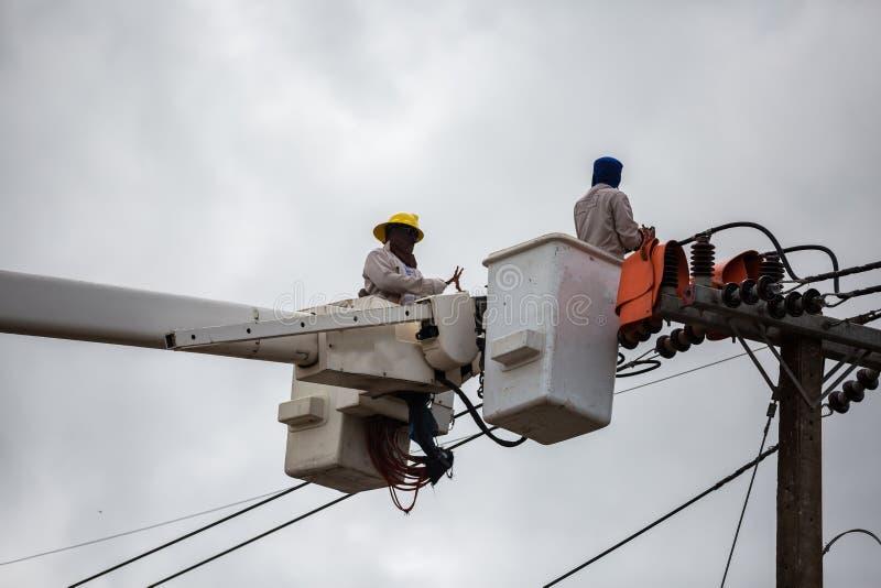 修理输电线的导线的在电力的电工 免版税库存照片