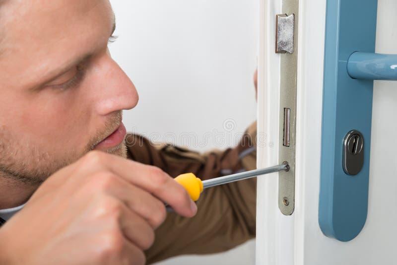 修理门锁的木匠 免版税库存图片