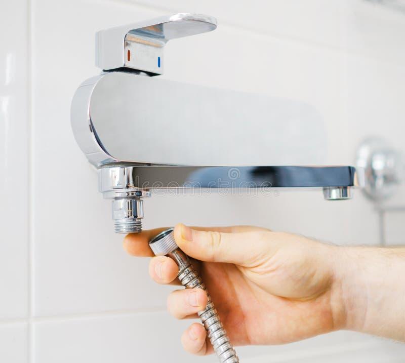 修理阵雨搅拌器的水管工手 免版税库存图片