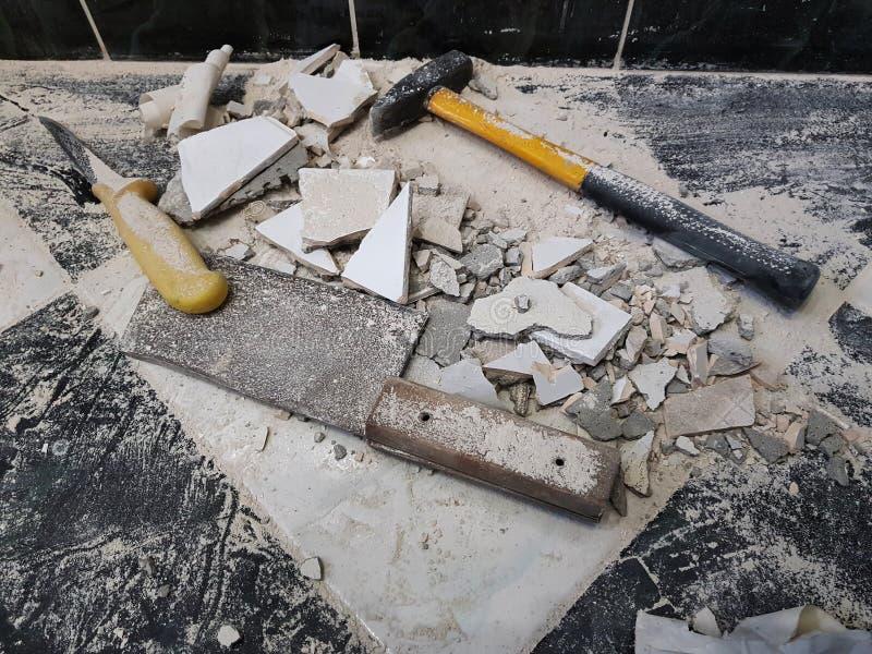 修理-与工具的大厦锤击,大锤、砍肉刀和一把刀子有瓦片碎片的  免版税图库摄影