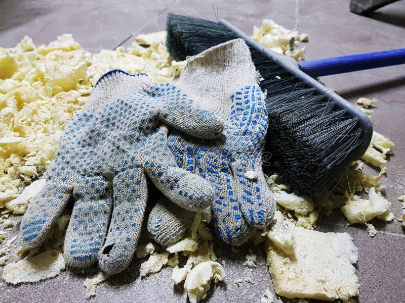 修理-整理在砖地上的泡沫、刷子和建筑手套 库存图片