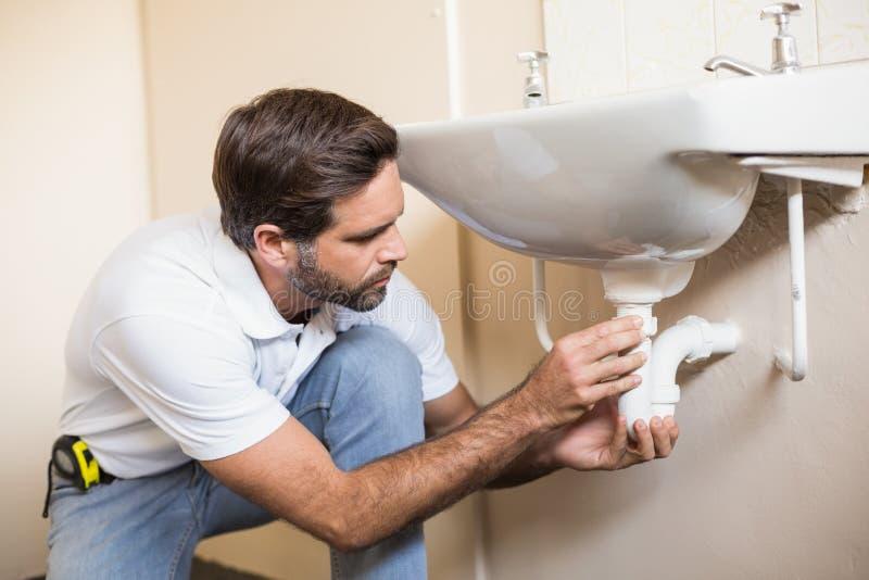 修理水槽的水管工在卫生间里 库存照片