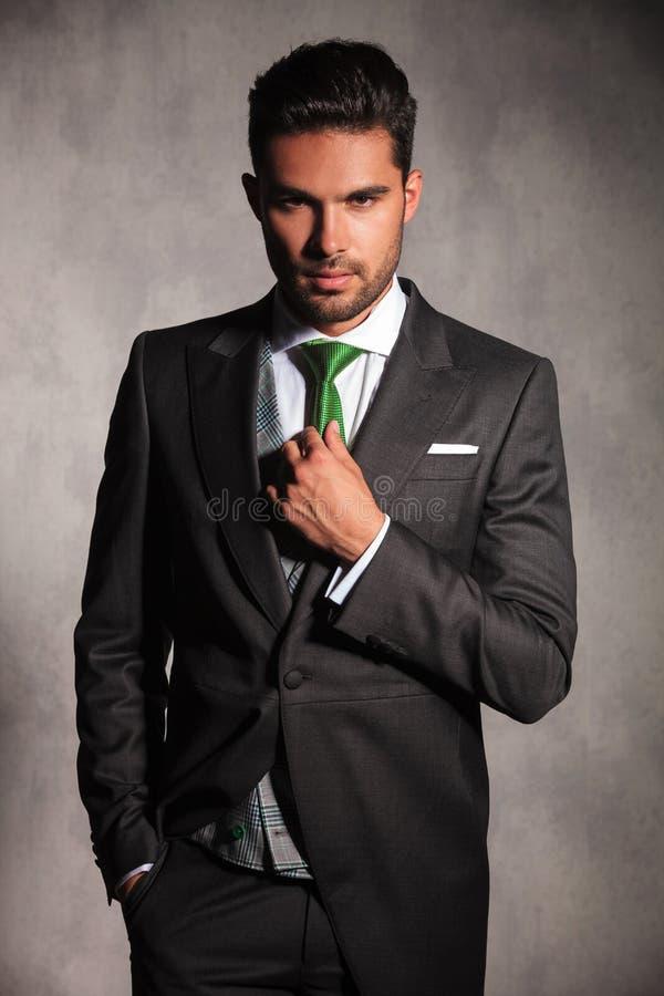 修理他的绿色领带的无尾礼服外套的年轻人 库存图片
