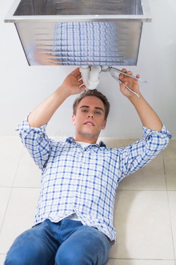 修理水盆流失的水管工在卫生间里 免版税库存图片