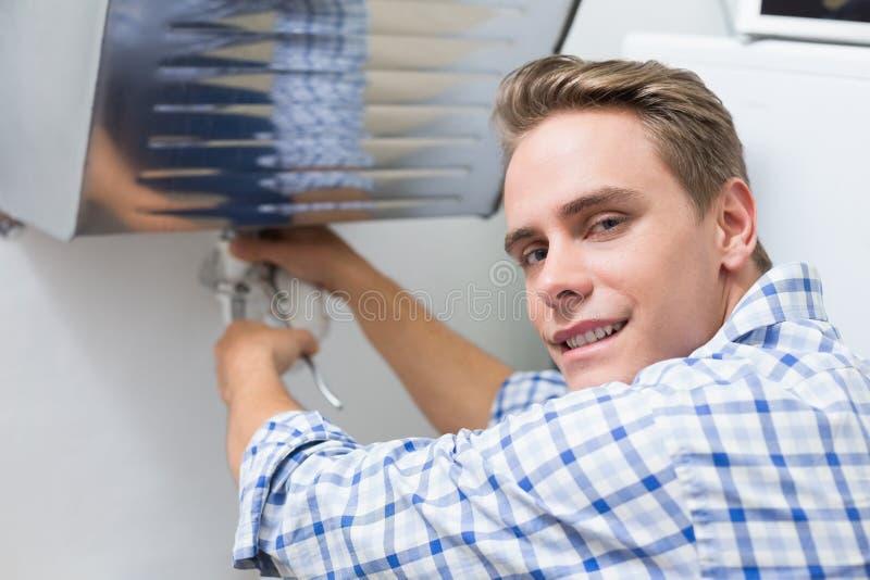 修理水盆流失的水管工在卫生间里 库存照片
