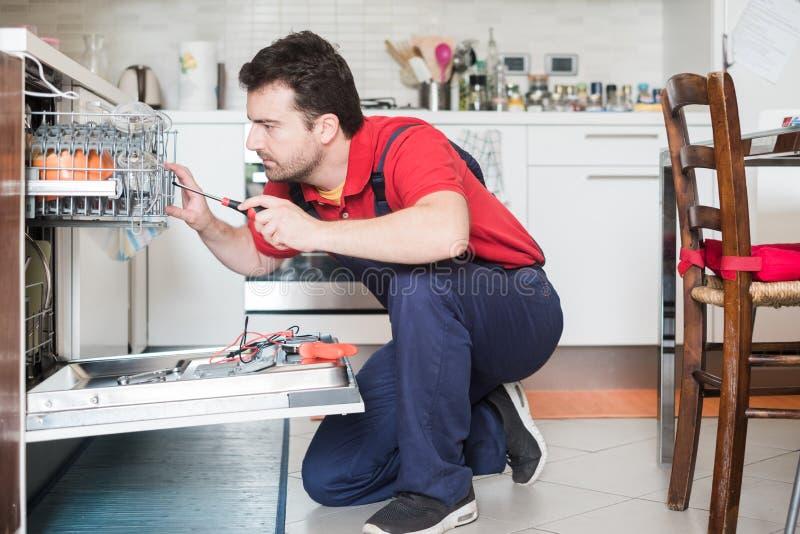 修理洗碗机的工作者在厨房里 库存照片