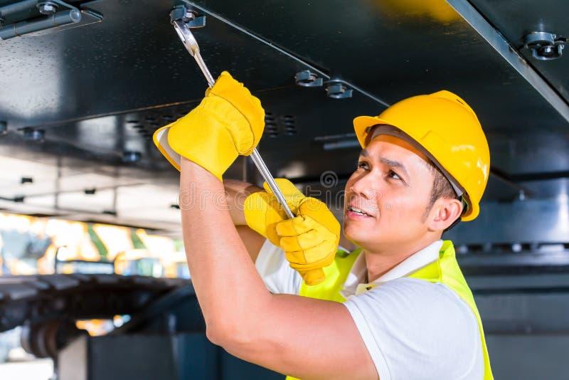 修理建筑车的亚裔技工 免版税库存照片