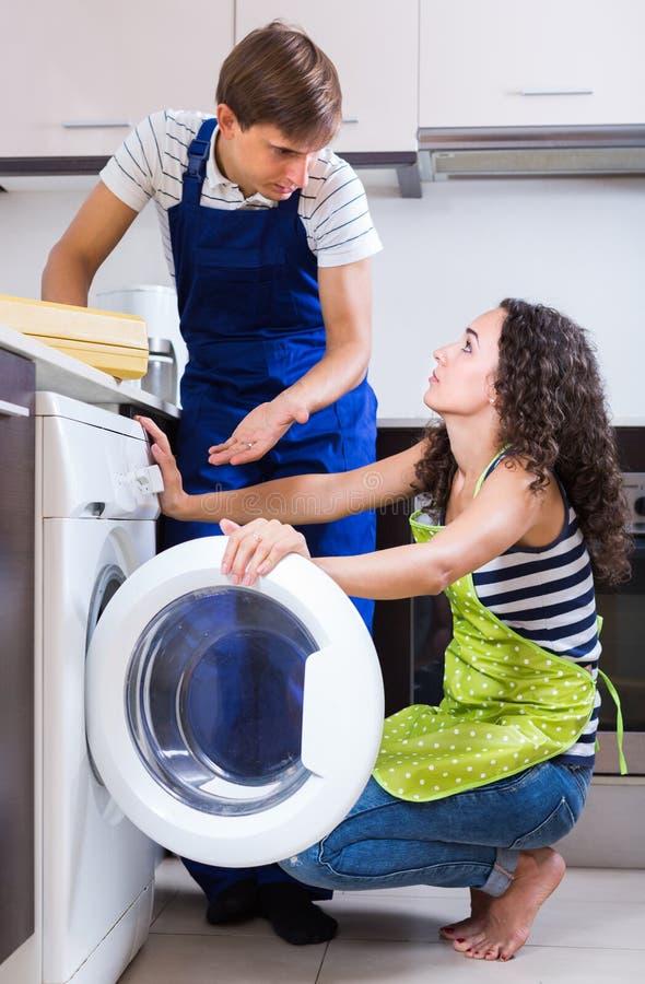 修理洗衣机和妇女的人 免版税库存照片
