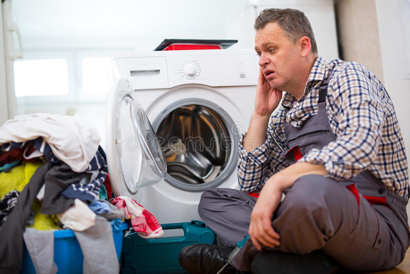 修理洗衣机的安装工在厨房里,坐在肮脏的洗衣店旁边 免版税图库摄影
