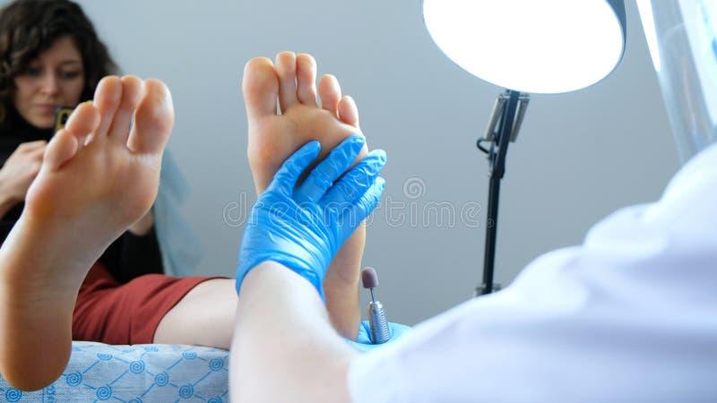 修脚大师导致在客户的脚的硬件削皮 免版税库存照片