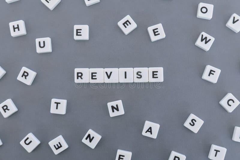 修订词由方形的信件词制成在灰色背景 免版税库存照片