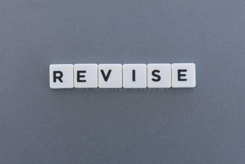 修订词由方形的信件词制成在灰色背景 库存照片