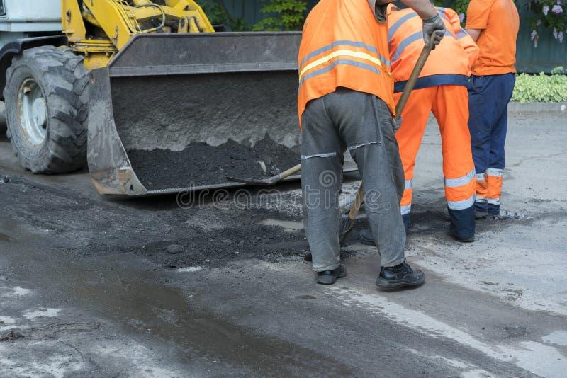 修路、产业和配合的工作者 涂柏油的摊铺机机器的建造者工作者在修理w的路街道期间 免版税库存照片