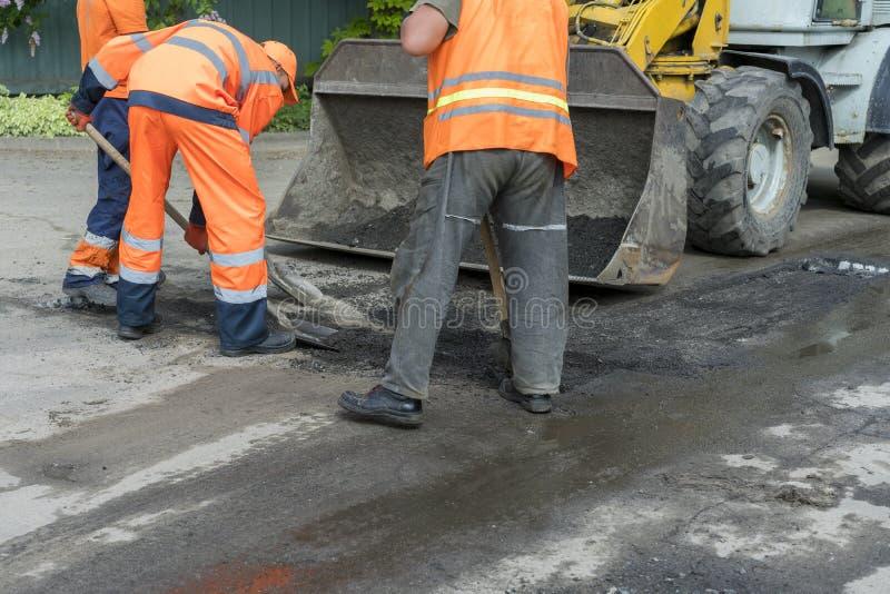 修路、产业和配合的工作者 涂柏油的摊铺机机器的建造者工作者在路街道期间 免版税库存照片