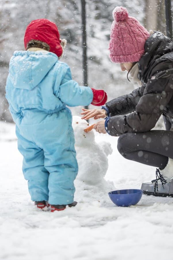 修造冬天雪人的母亲和孩子 图库摄影