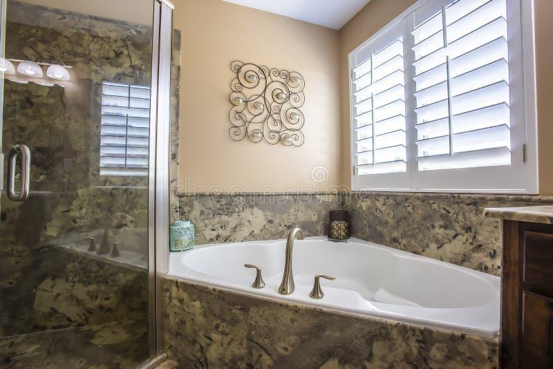 修造在浴缸在一个卫生间的角落有墙壁装饰和窗口的 库存图片