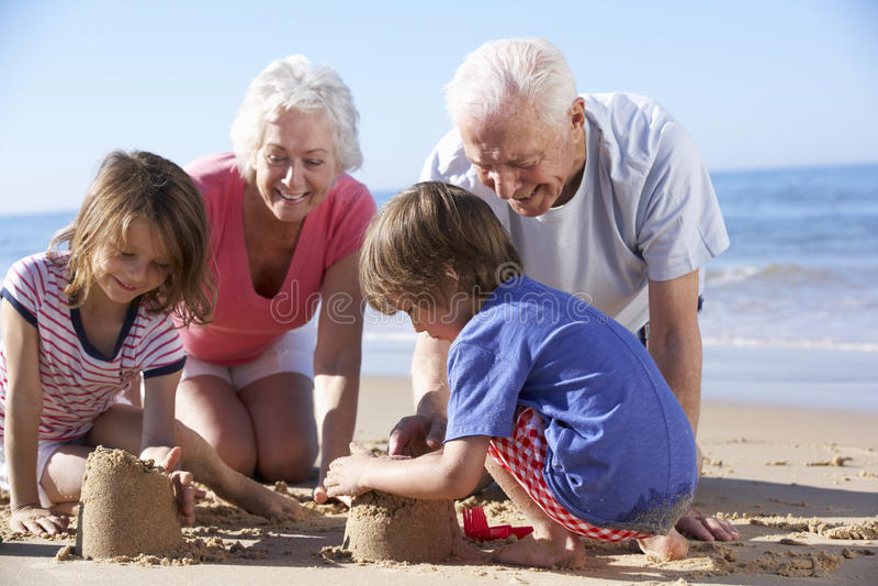 修造在海滩的祖父母和孙沙堡 库存图片
