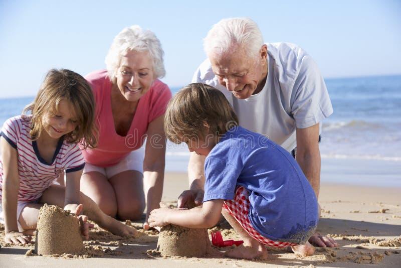 修造在海滩的祖父母和孙沙堡 库存照片
