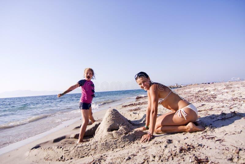 修造沙子城堡的母亲和女儿 库存照片