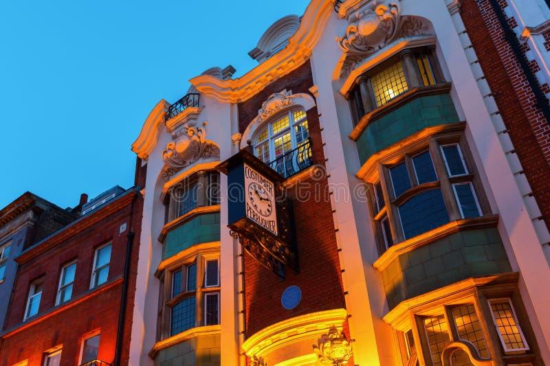 修造用古色古香的时钟的Perruquier服装商在唐人街,伦敦 库存照片