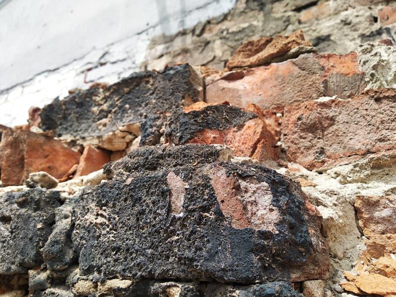 修造的房子的红砖 在地方毁坏的房子,被烧的黑砖,材料被终止的片断  ? 免版税库存图片