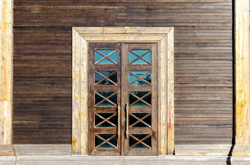 修造的门面-木墙壁,与玻璃插入物的一个门 库存图片