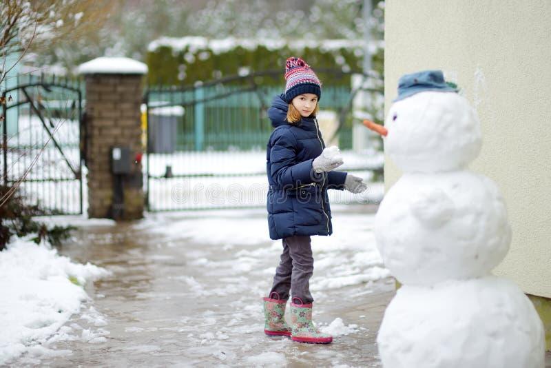 修造雪人的可爱的小女孩在后院 使用在雪的逗人喜爱的孩子 免版税库存照片