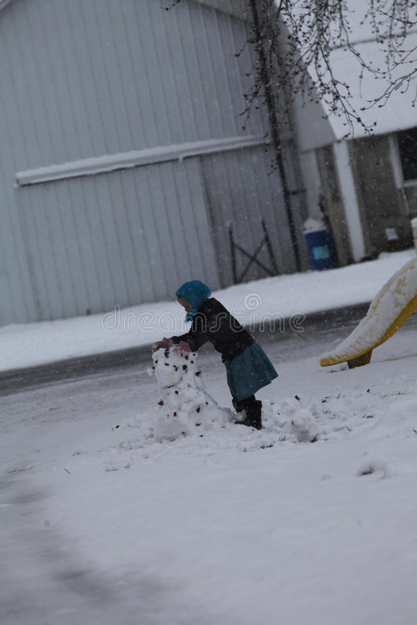 修造雪人的年轻门诺派中的严紧派的女孩 库存图片
