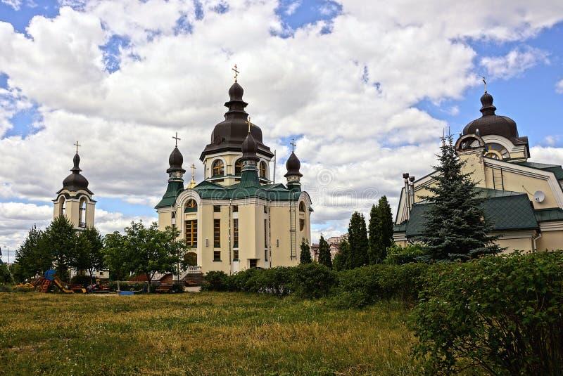 修道院和教会在反对天空和云彩的一个绿色公园 库存照片