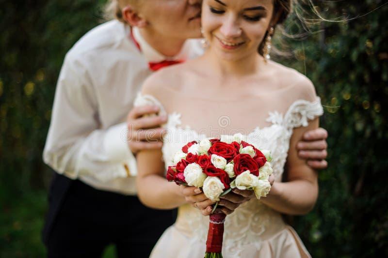 修饰亲吻他的年轻和美丽的新娘在绿色树背景中  免版税库存照片