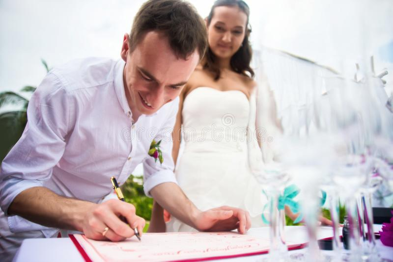 修饰在婚姻和微笑的注册的标志文件 年轻人夫妇签署婚礼文件 室外婚礼蜡膜 库存图片